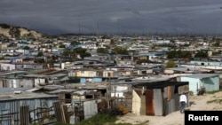 Residents walk through shacks in Cape Town's crime-ridden Khayelitsha township, July 9, 2012.