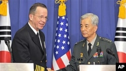 US Navy Adm. Mike Mullen, left, the US chairman of the Joint Chiefs of Staff, and South Korean Gen. Han Min-Koo, right, chairman of South Korean Joint Chiefs of Staff, shake hands after their joint press conference at the Defense ministry in Seoul, Dec 8,