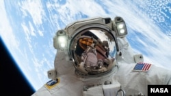 Pictured here with Earth in the background, NASA astronaut Mike Hopkins, Expedition 38 Flight Engineer, takes a spacewalk, December 2013. (Image Credit: NASA)