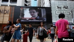 People cross a street in front of a monitor showing file footage of Edward Snowden, a former contractor for the U.S. National Security Agency (NSA), with a news tag (L) saying he has left Hong Kong, outside a shopping mall in Hong Kong, June 23, 2013.
