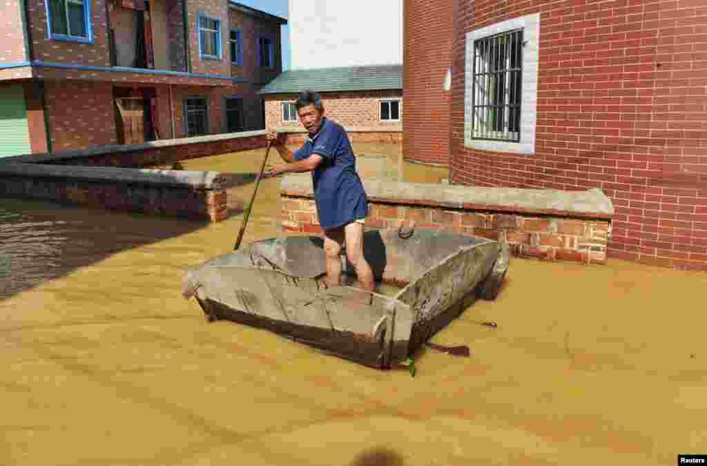 در سیل چین، این مرد از وسیله ای جای قایق استفاده می کند.