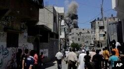 巴勒斯坦人在街上觀看以色列空襲加沙地帶後翻起的濃煙。
