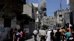Palestinos observan el humo y el povo que se levanta tras un ataque israelí en Gaza.