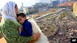 Mwanamke wa Misri akiangalia umati wa waandamanaji kutokea nyumbani kwake Cairo.