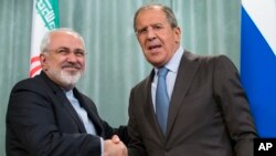 FILE - Iranian Foreign Minister Mohammad Javad Zarif (L) and Russian Foreign Minister Sergei Lavrov are seen shaking hands.