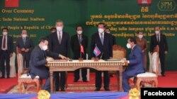 រដ្ឋមន្ត្រីការបរទេសចិន លោក វ៉ាង យី (Wang Yi) (ឆ្វេង) ឈរនៅជិតលោកនាយករដ្ឋមន្ត្រី ហ៊ុន សែន ក្នុងពិធីប្រគល់និងទទួលពហុកីឡដ្ឋានជាតិមរតកតេជោ ដែលជាជំនួយរបស់សមភាគីចិន នៅភ្នំពេញ ថ្ងៃទី១២ ខែកញ្ញា ឆ្នាំ២០២១។ (រូបថត Facebook/Samdech Hun Sen, Cambodian Prime Minister)