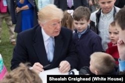 President Donald J. Trump joins kids coloring and signing cards for U.S. Troops, at the White House Easter Egg Roll, April 2, 2018, in Washington, D.C. (Official White House Photo by Shealah Craighead)
