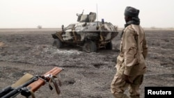 A Chadian soldier walks past an armored vehicle that the Chadian military said belonged to insurgent group Boko Haram that they destroyed in battle in Gambaru, Nigeria, Feb. 26, 2015.