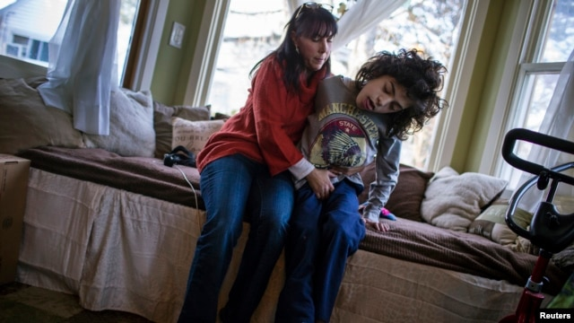 Missy Miller sits with her epileptic son, Oliver (R), in their home near Atlantic Beach, New York, Jan. 7, 2014.