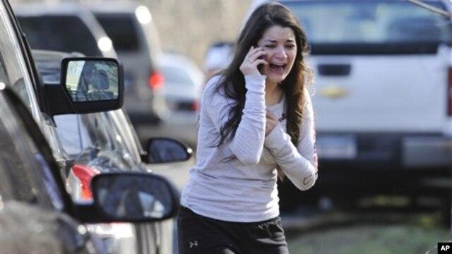 Mulher desesperada aguarda notícias sobre a sua irmã, uma professora na Escola Primária de Sandy Hook, em Newtown, no estado de Connecticut.