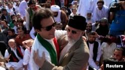 Ulama Sufi dan pempimpin partai politik Pakistan Awami Tehreek (PAT), Tahir ul-Qadri (kanan) menyambut Imran Khan, politisi oposisi Pakistan seusai sholat Idul Adha di depan gedung parlemen (Foto: dok).