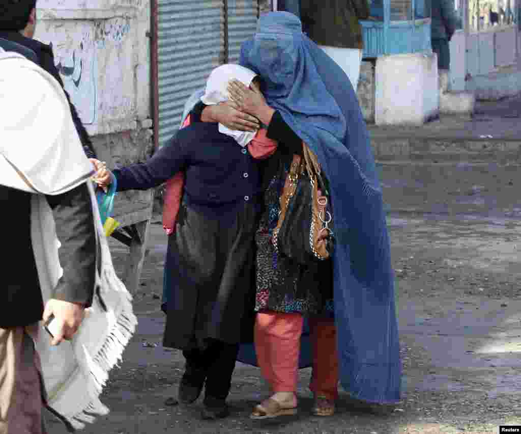 A woman and her daughter walk away after a blast near the Pakistani consulate in Jalalabad, Afghanistan. Afghan security forces exchanged fire with gunmen barricaded in a house near the Pakistan consulate in the eastern city of Jalalabad after a suicide bomber blew himself up, officials said.