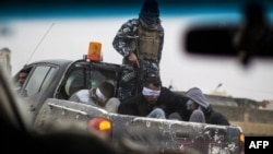 Quatre hommes membres présumés du groupe de l'État islamique (IS) arrêtés et transportés dans un véhicule à Mossoul, 2 décembre 2016.