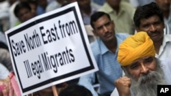 FILE - An Indian supporter of the Bharatiya Janata Party (BJP) holds a placard during a protest against what participants say is the illegal migration of Muslims from Bangladesh to the northeastern state of Assam, in New Delhi, India, Aug. 18, 2012.