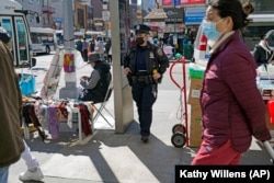 Joanna Derkacz, seorang polisi dari Kepolisian Kota New York, mengamati para pejalan kaki di Main Street, Flushing, kawasan Queens, di New York, Selasa, 30 Maret 2021. (Foto: Kathy Willens/Associated Press)