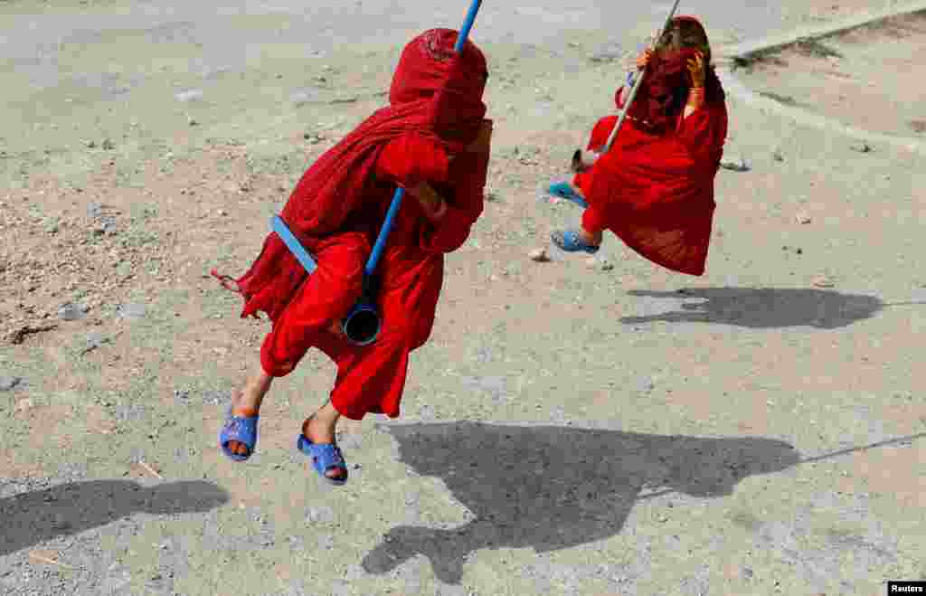 Girls ride on swings during the first day of the Muslim holiday of the Eid al-Adha, in Kabul, Afghanistan, Aug. 11, 2019.