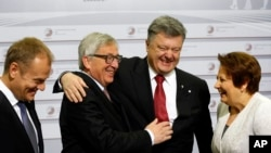 European Commission President Jean-Claude Juncker, center left, greets Ukrainian President Petro Poroshenko, center right, and Latvia Prime Minister Laimdota Straujuma, right, during arrivals at the Eastern Partnership summit in Riga, Latvia, May 22, 2015.