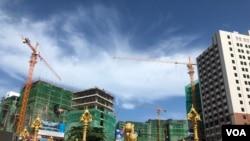 柬埔寨西南部西港努克港市中心的狮子雕塑被中国人兴建的高楼所包围。