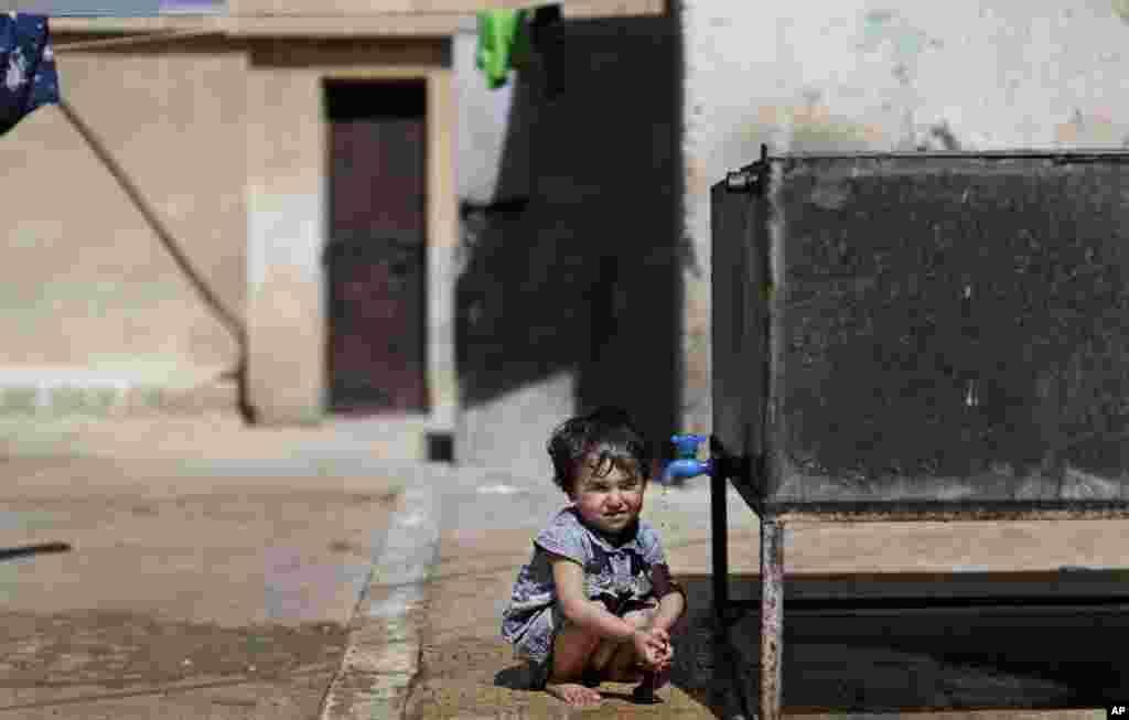 Seorang anak Suriah yang ditinggalkan keluarganya akibat pertempuran antara pasukan pemerintah dan pemberontak Suriah, minum air dari sebuah tangki air minum di sebuah sekolah di Aleppo (10/9).