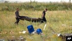 Nhân viên Bộ tình huống khẩn cấp Ukraine khiêng thi thể nạn nhân tại hiện trường vụ rơi máy bay Malaysia gần làng Hrabove, miền đông Ukraine, ngày 19/7/2014.