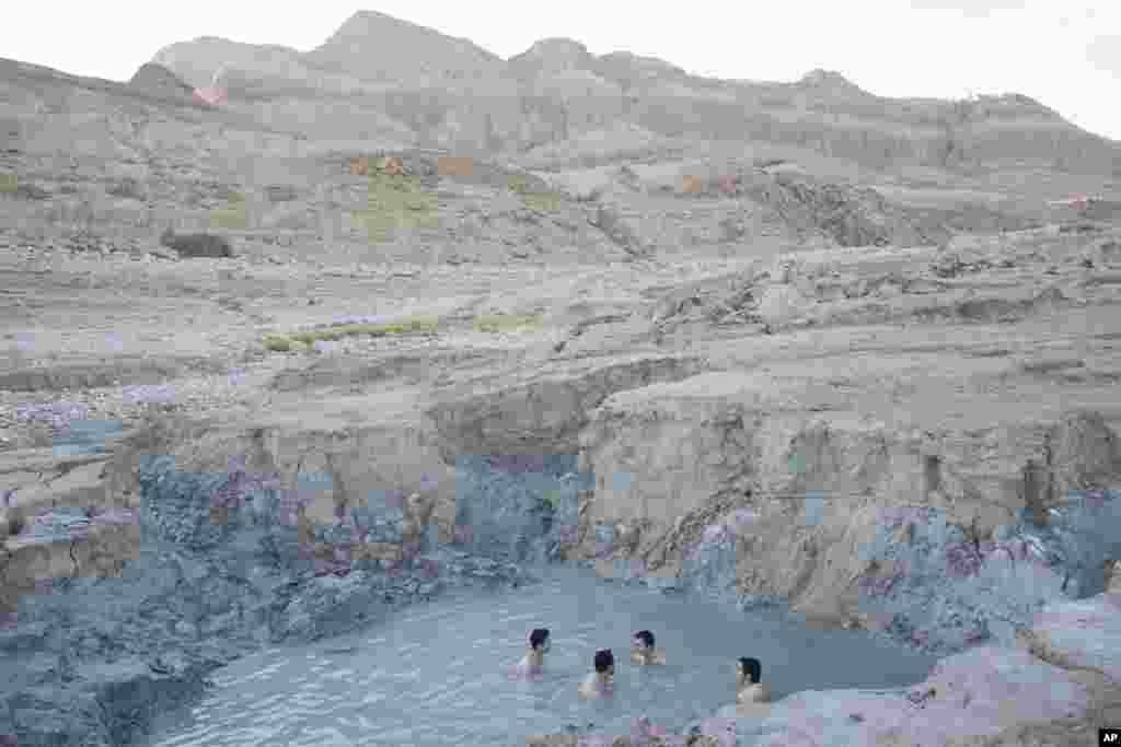 لذت بردن چند مرد اسرائیلی از یک چشمه آب گرم در ساحل دریای مرده در اسرائیل.