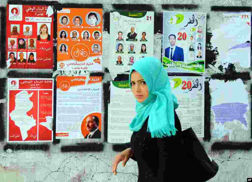 A woman walks past electoral campaign posters for the upcoming parliamentary elections in Tunis, Tunisia.