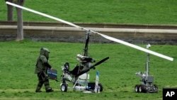 A member of a bomb squad checks a gyrocopter sitting on the West Lawn of the Capitol in Washington, April 15, 2015.