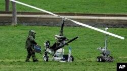 Anggota penjinak bom AS memeriksa helikopter kecil yang mendarat di halaman gedung Kongres AS, Rabu (15/4).