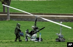 A member of a bomb squad checks a small helicopter after a man landed on the West Lawn of the Capitol, April 15, 2015.