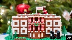 FILE - A Lego model of the White House, one of 56 Lego gingerbread houses, one for each state and territory, is displayed in the State Dining Room at the White House during a preview of the 2016 holiday decor, in Washington, Nov. 29, 2016.