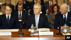Italian Premier Mario Monti, center, is flanked by Foreign Minister Giulio Terzi di Sant'Agata, left, during a meeting in Rome, December 15, 2011.