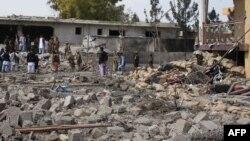 سیکیورٹی عہدے دار افغان قصبے لشکر گاہ میں ایک خودکش دھماکے کے مقام کا جائزہ لے رہے ہیں۔ (فائل فوٹو)