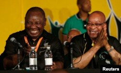 FILE: South Africa's President Jacob Zuma, right, jokes with his deputy, Cyril Ramaphosa, after Zuma's re-election in 2012.