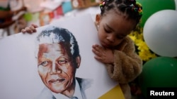 Two-year-old Precious Mali holds a picture of former South African President Nelson Mandela as well-wishers gather outside the Medi-Clinic Heart Hospital where Mandela is being treated in Pretoria June 28, 2013.
