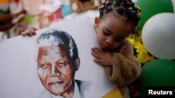 Bé Precious Mali, 2 tuổi, với hình cựu Tổng thống Nam Phi Nelson Mandela giữa những người tập trung trước bệnh viện nơi ông Mandela đang được điều trị ở Pretoria, ngày 28/6/2013.