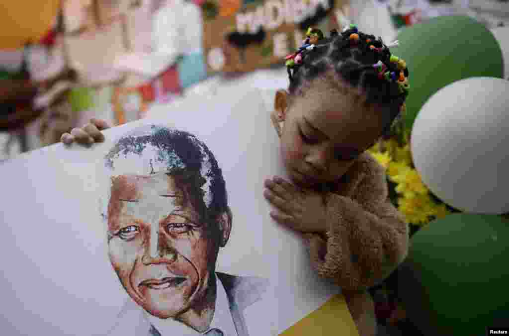 Two-year-old Precious Mali holds a picture of former South African President Nelson Mandela as well-wishers gather outside the Medi-Clinic Heart Hospital where Mandela is being treated in Pretoria.