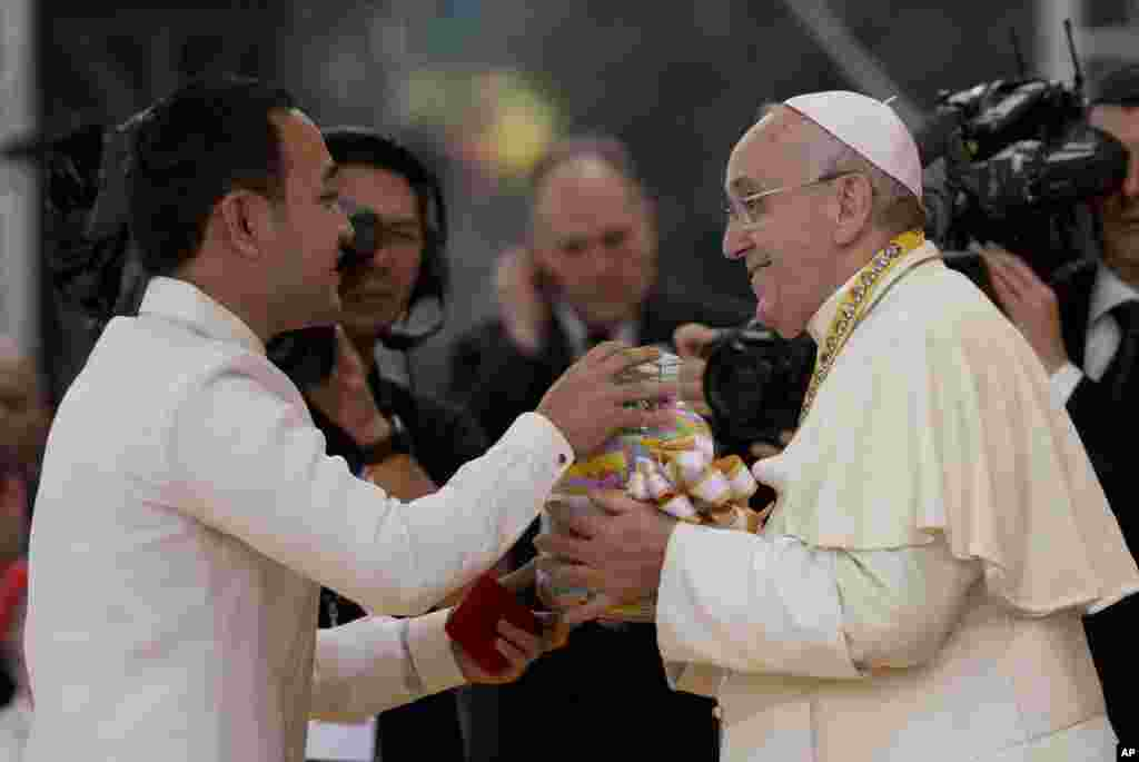 Pope Francis is presented with a jar containing messages of former street children during his meeting with the youth in Santo Tomas University in Manila, Jan. 18, 2015.