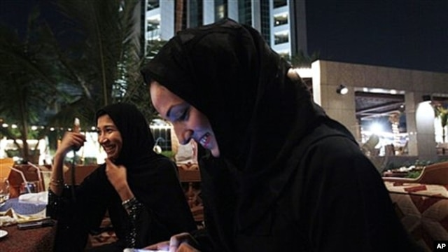 Saudi woman with cellphones smoke tobacco from a waterpipe as they drink coffee in Jeddah, Saudi Arabia, Nov. 2010 (file photo).