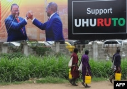 People walk past a campaign poster of Kenya's President Uhuru Kenyatta and Deputy President William Ruto, in Nairobi, Oct. 23, 2017, ahead of the repeat elections.