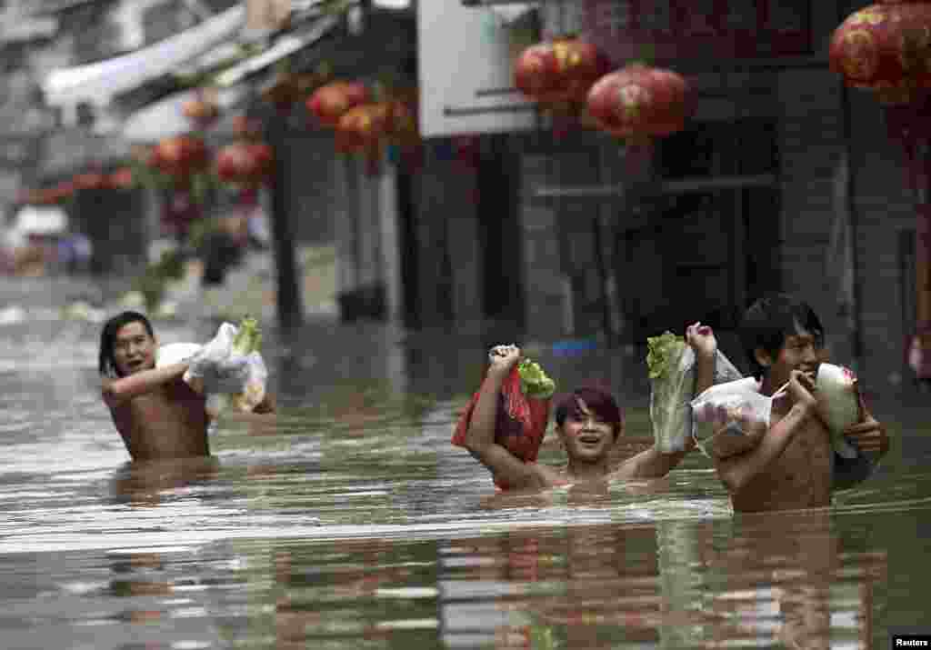 Residents raise bags of groceries as they walk on a flooded street after Typhoon Fitow hit Daxi township of Wenling, Zhejiang province, China, Oct. 8, 2013.
