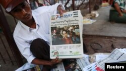 A news vendor displays local newspapers on a street in Yangon November 9, 2015. Voting unfolded smoothly in Myanmar on Sunday with no reports of violence to puncture a mood of jubilation marking the Southeast Asian nation's first free nationwide election