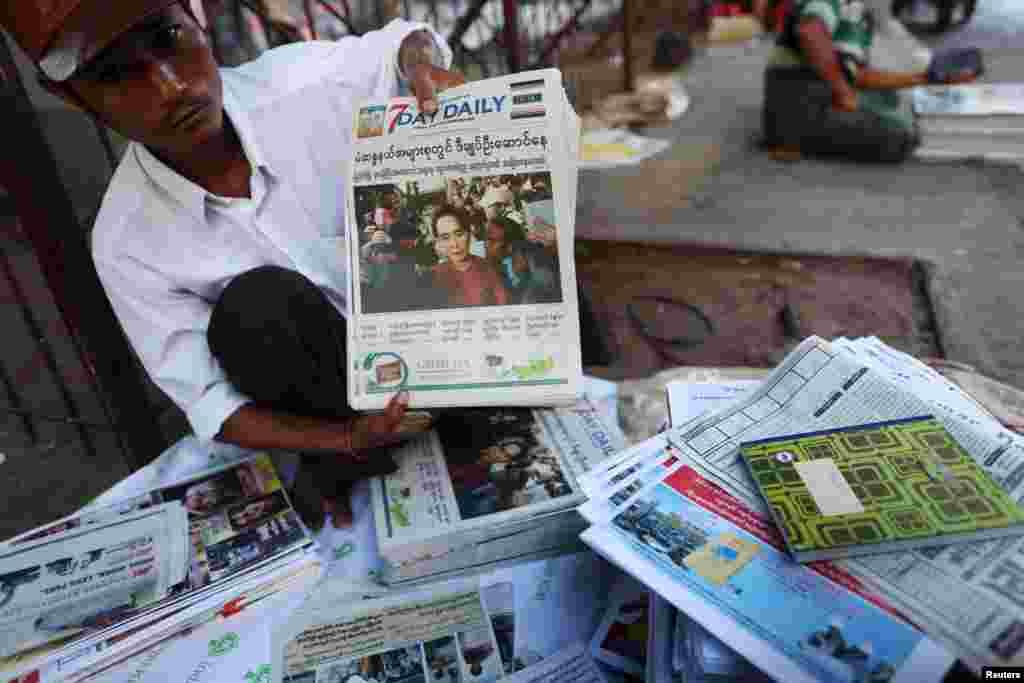Seorang penjual koran memperlihatkan koran lokal di sebuah jalan di Yangon, Myanmar (9/11).(Reuters/Soe Zeya Tun)