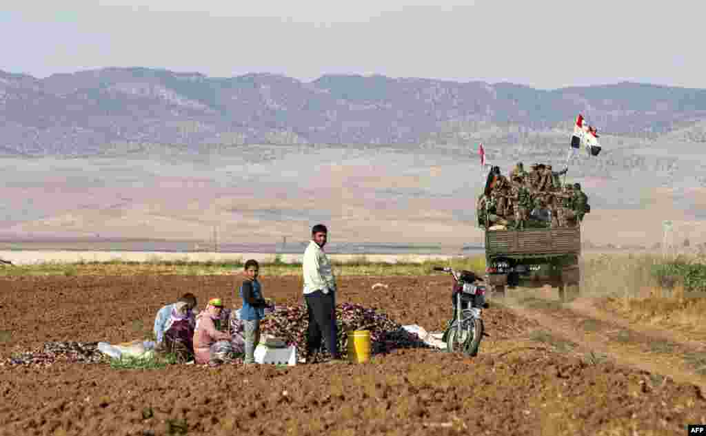 Syrian government soldiers ride in the back of a truck with national flags past people sitting in a field with harvested aubergines, as government forces deploy for the first time in the eastern countryside of the city of Qamishli in the northeastern Hasakah province, Nov. 5, 2019.