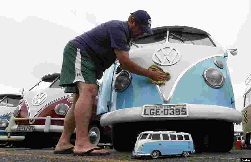 ایک شخص اپنی فولکس ویگن کو صاف کر رہا ہے۔