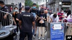 在北京的一條旅遊購物街,人們用智能手機向保安出示健康碼(2021年8月3日)。