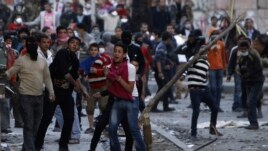 Anti-Morsi protesters throw stones towards riot police during clashes in Simon Bolivar Square, which leads to Tahrir Square, in Cairo, Egypt, January 30, 2013.