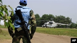 A U.N. peacekeeper in Ivory Coast stands guard by an UN helicopter used to transport officials and journalists from UNOCI headquarters to the Hotel du Golf, the temporary headquarters of Alassane Ouattara, in Abidjan, 3 Jan 2011