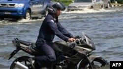 Một sĩ quan không quân Thái Lan cưỡi xe gắn máy qua con đường Paholyothin ngập gần sân bay Don Muang ở Bangkok, ngày 25/10/2011