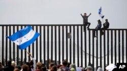 Migran Amerika Tengah duduk di atas dinding perbatasan pantai di San Diego saat berlangsungnya pertemuan para migran yang tinggal di kedua sisi perbatasan, 29 April 2018.