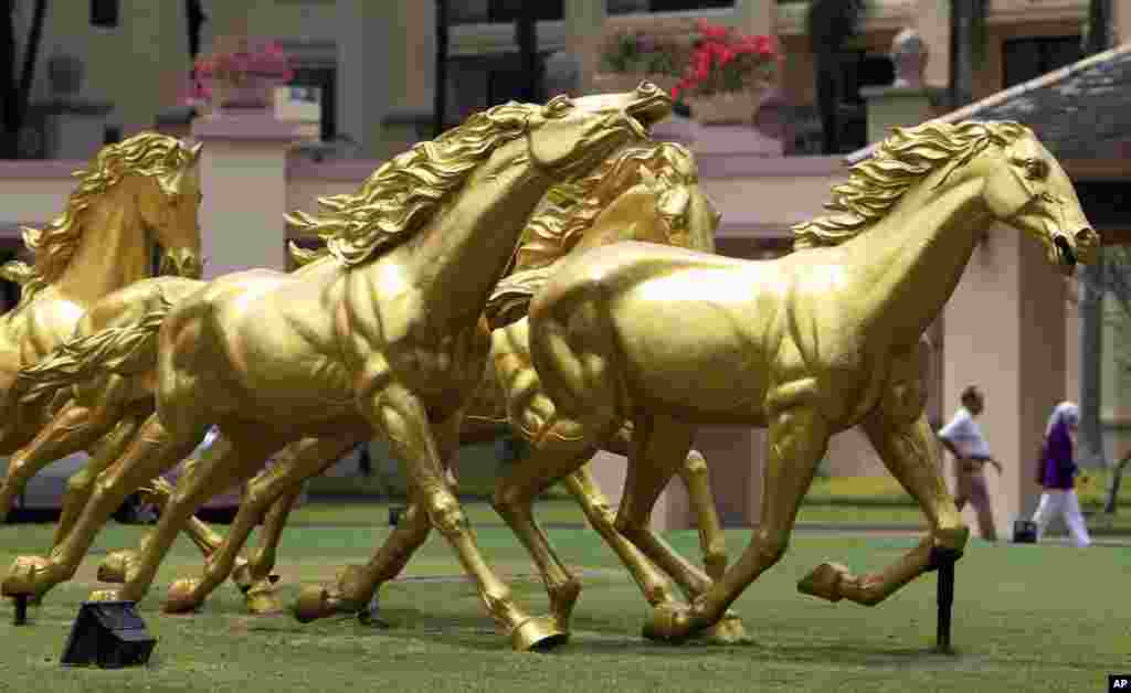 People walk past golden horse statues on display in front of a hotel in Kuala Lumpur, Malaysia.
